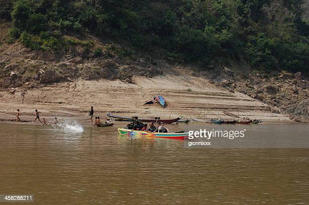 Speed boat and children playing on Mekong river, Laos