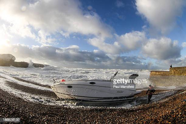 CONTENT] A speed boat is left stranded on Brighton beach after a storm Crashing waves seen in background hitting Brighton Marina wall