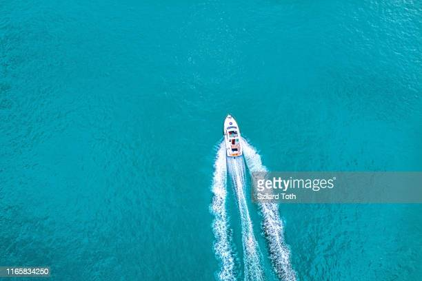 speed boat on  azure sea in turquoise blue water -  birdseye aerial view of boat - nautical vessel stock pictures, royalty-free photos & images