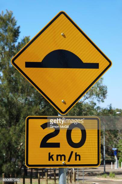 Speed bump ahead traffic warning sign and 20 kilometre per hour speed limit sign