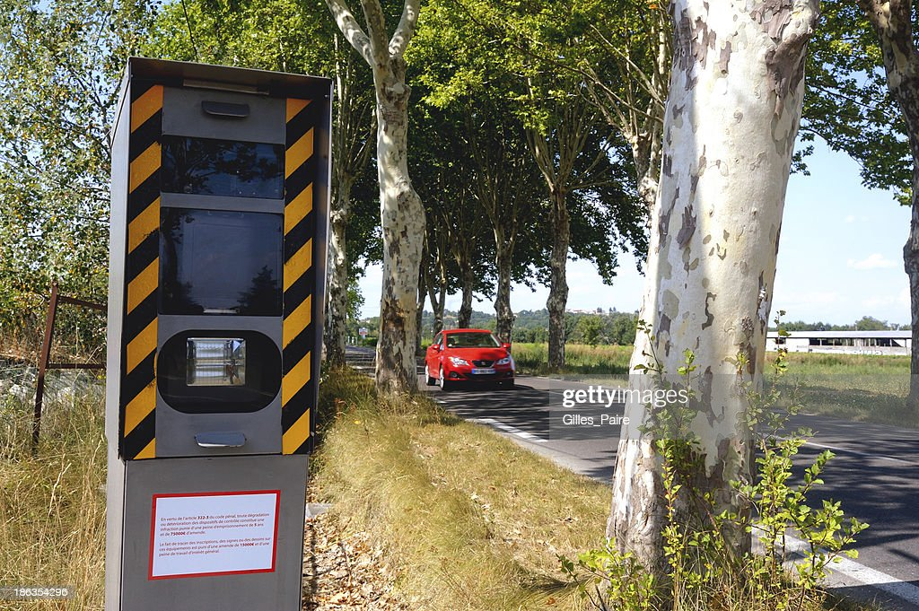 Speed camera on the side of a tree lined road