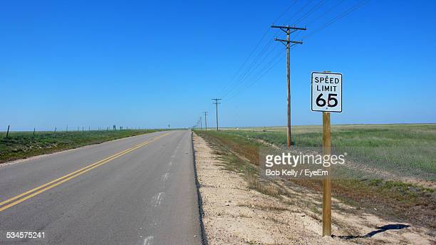speed limit 65 sign and electricity pylon by country road against clear blue sky - speed limit sign stock photos and pictures