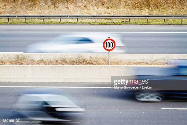 speed limit sign amidst blur cars on street - speed limit sign stock photos and pictures