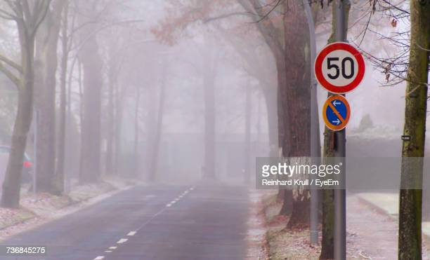speed limit sign by road amidst trees during foggy weather - number 50 stock pictures, royalty-free photos & images