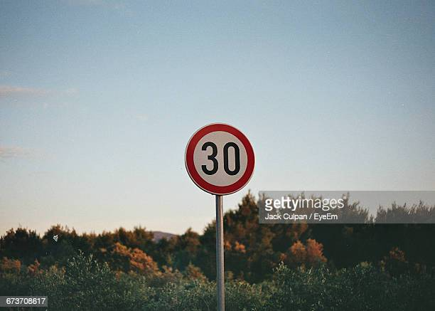 speed limit sign by trees against sky - speed limit sign stock photos and pictures