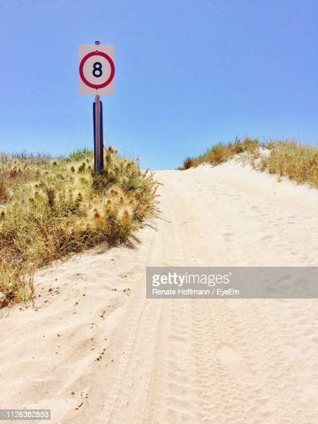 Speed Limit Sign On Sand Dune Against Clear Blue Sky