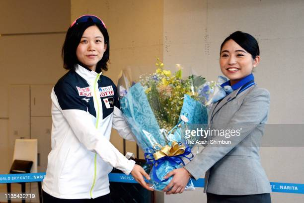 Speed skater Miho Takagi receives a flower bouquet on arrival at Narita International Airport on March 12 2019 in Narita Chiba Japan