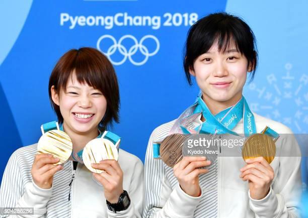 Speed skating sisters Nana Takagi and Miho Takagi of Japan show off their medal haul at a press conference for medal winners at the Pyeongchang...