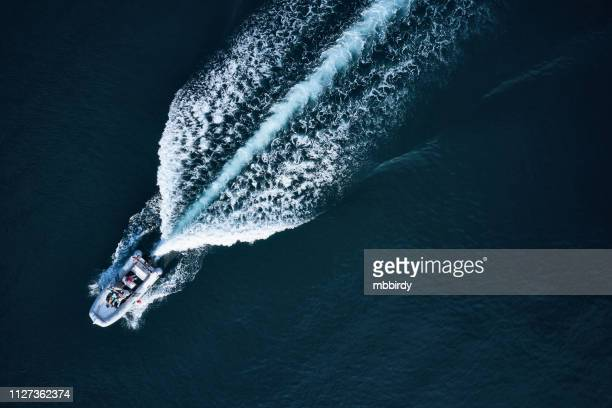 speedboat racing along the open sea - inflatable raft stock pictures, royalty-free photos & images