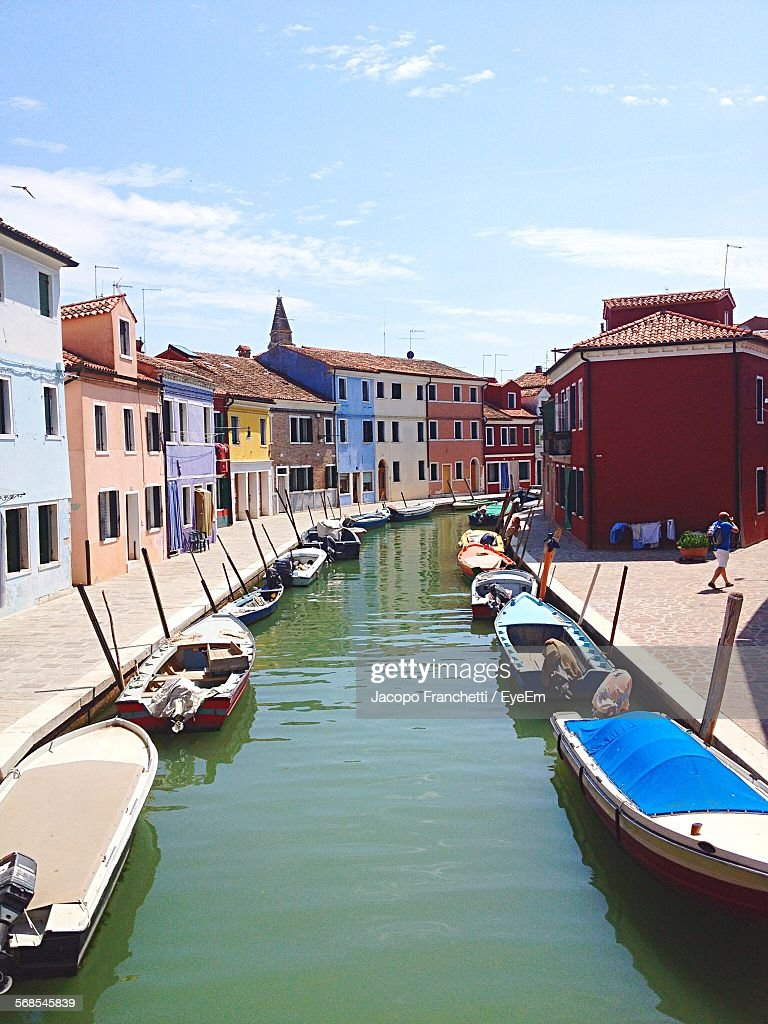 Speedboats Moored On Canal Amidst Multi Colored Houses Against Sky : Stock Photo