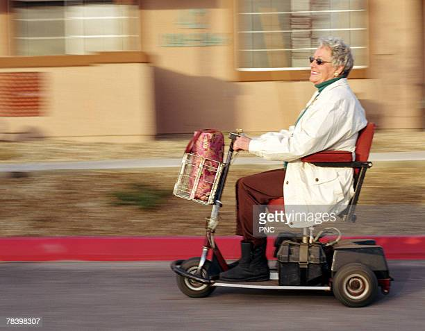 speeding senior on motorized scooter - mobility scooter stock photos and pictures