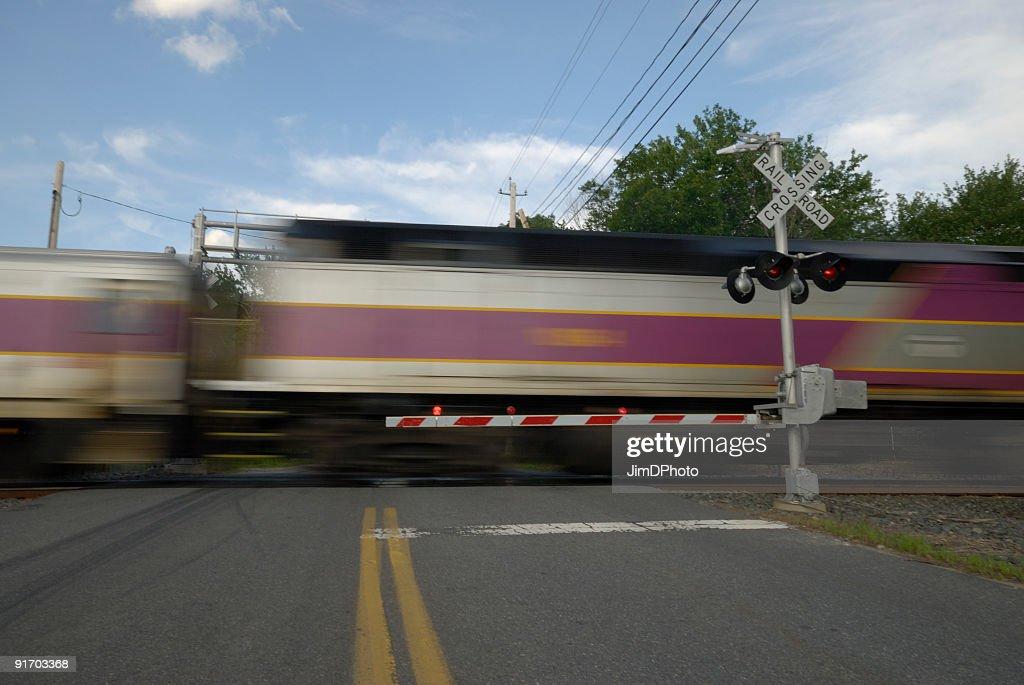 Speeding train crossing a street : Stock Photo