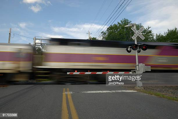 speeding train crossing a street - railroad crossing stock pictures, royalty-free photos & images