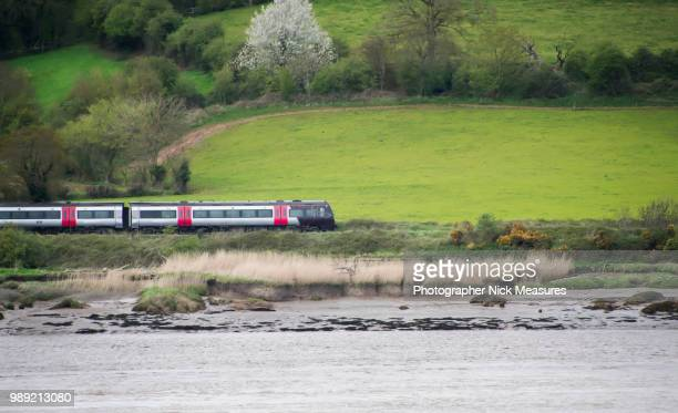 speeding train running through the english country side. - train stock photos and pictures