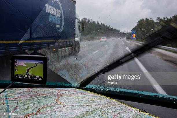 Speeding truck overtaking car on highway during heavy rain shower seen from inside of vehicle with GPS and road map on dashboard