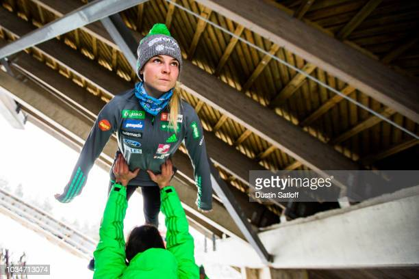Spela Rogelj of Slovenia prepares with her coach underneath the jump before the start of the Women's Ski Jumping HS100 qualification rounds during...