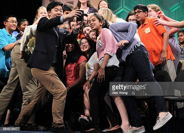 Spellers who have been eliminated from the competition take a selfie also known as 'spellfie' during a live broadcast commercial break of final...