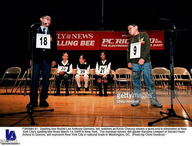 Spelling bee finalist Lee Anthony Germino left watches as Kevin Cheung misses a word and is eliminated at New York City's spelling bee finals March...