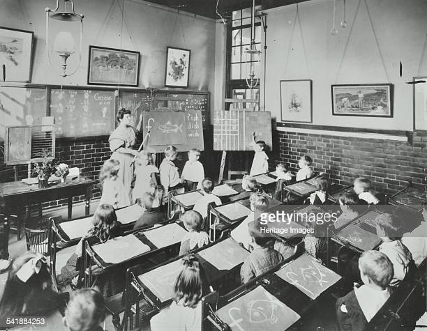 Spelling lesson, Southfields Infants' School, Wandsworth, London, 1907. Children are being taught the formation of the word 'fish' by a teacher. The...
