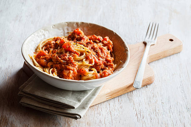 spelt whole grain spaghetti with vegan bolognese made of green spelt and sunflower seed - pasta plate stock pictures, royalty-free photos & images