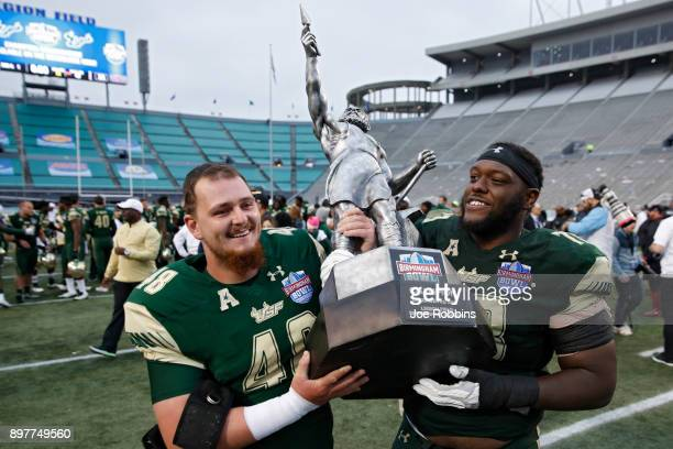 Spencer Adkinson and Jeremi Hall of the South Florida Bulls carry the championship trophy following the Birmingham Bowl against the Texas Tech Red...