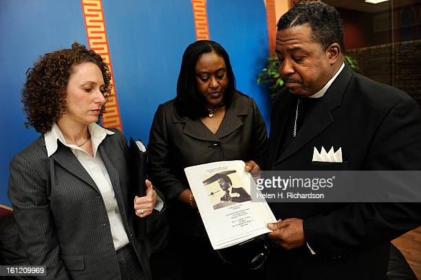 Spencer Booker right and his wife Gail look at a picture of his brother Marvin Booker from his funeral program with attorney Mari Newman and watch...