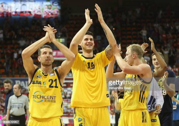 Spencer Butterfield Bogdan Radosavljevic and Luke Sikma of ALBA Berlin celebrate their victory of the first playoff game of the German Basketball...