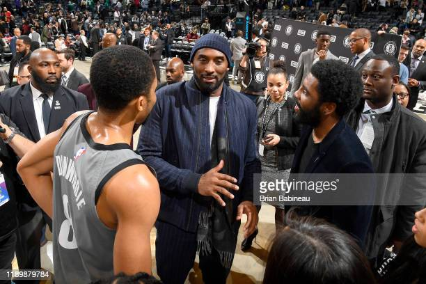 Spencer Dinwiddie, and Kyrie Irving of the Brooklyn Nets talk with Former NBA Player, Kobe Bryant after the game Atlanta Hawks on December 21, 2019...