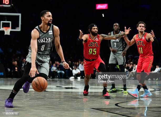 Spencer Dinwiddie of the Brooklyn Nets dribbles the ball up court as DeAndre' Bembry and Trae Young of the Atlanta Hawks react during the first half...