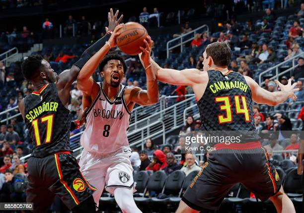 Spencer Dinwiddie of the Brooklyn Nets drives between Dennis Schroder and Tyler Cavanaugh of the Atlanta Hawks at Philips Arena on December 4 2017 in...