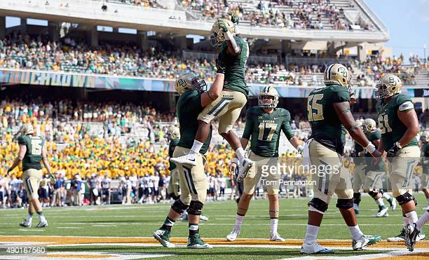 Spencer Drango of the Baylor Bears and Seth Russell of the Baylor Bears celebrate with Johnny Jefferson of the Baylor Bears after scoring a touchdown...