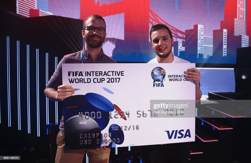 Spencer 'Gorilla' Ealing (R) of England is presented with his cheque by Alexander Shapiro of Visa after his victory in the final against Kai 'Deto' Wollin of Germany during day three of the FIFA Interactive World Cup 2017 Grand Final at Central Hall Westminster on August 18, 2017 in London, England.