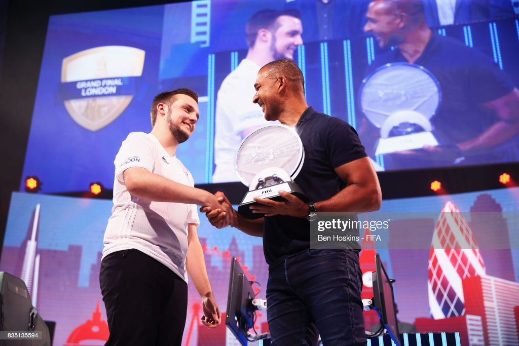 Spencer 'Gorilla' Ealing of England is presented with the trophy by Ruud Gullit after his victory in the final against Kai 'Deto' Wollin of Germany during day three of the FIFA Interactive World Cup 2017 Grand Final at Central Hall Westminster on August 18, 2017 in London, England.