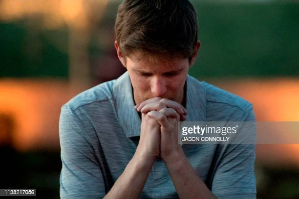 Spencer Greenlee a senior a Columbine High School prays at the Columbine Memorial at Clement Park in Littleton Colorado during a community vigil for...