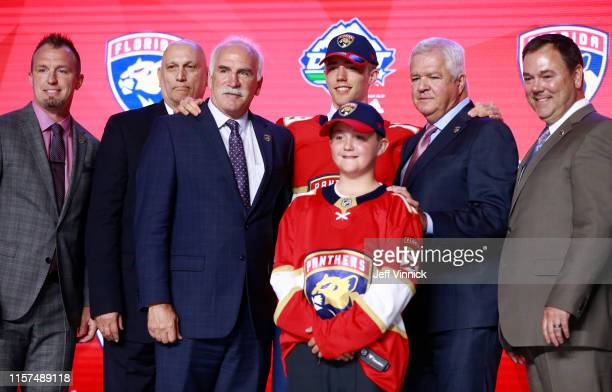 Spencer Knight, 12th overall pick by the Florida Panthers, poses for a group photo onstage with team personnel during the first round of the 2019 NHL...