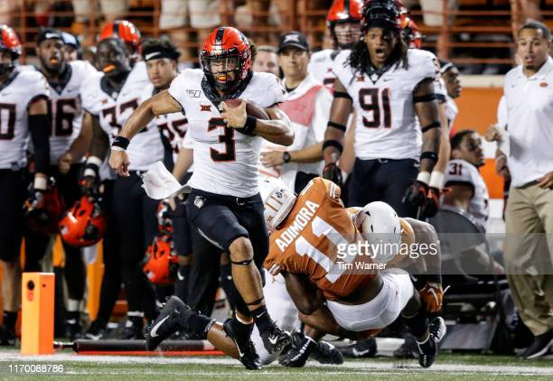 Spencer Sanders of the Oklahoma State Cowboys scrambles for a first down in the fourth quarter defended by Chris Adimora of the Texas Longhorns and...