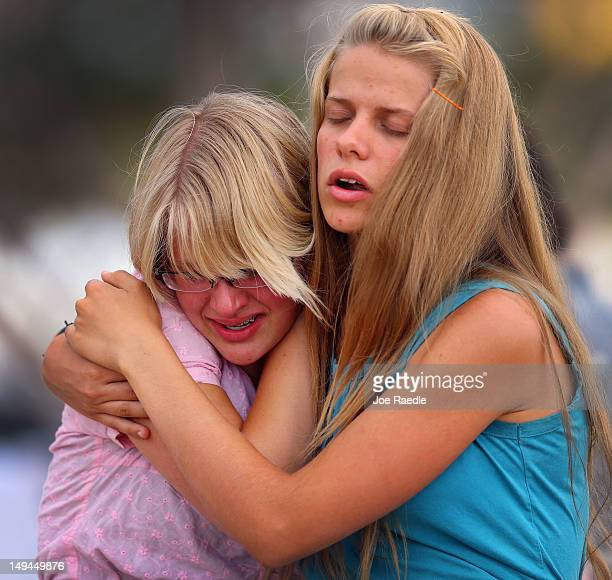 Spencer Sikkema comforts her sister Daviah Sikkema during a visit to a memorial setup across the street from the Century 16 movie theatre on July 28...