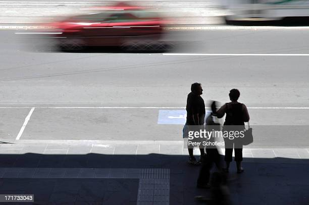 Spencer Street, Melbourne, Australia. December 2008. Three silhouetted figures stand in the shade as cars blurr along the busy road in the...