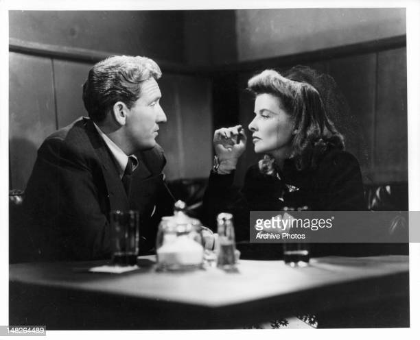 Spencer Tracy and Katharine Hepburn having drinks together at small table in a scene from the film 'Woman Of The Year', 1942.