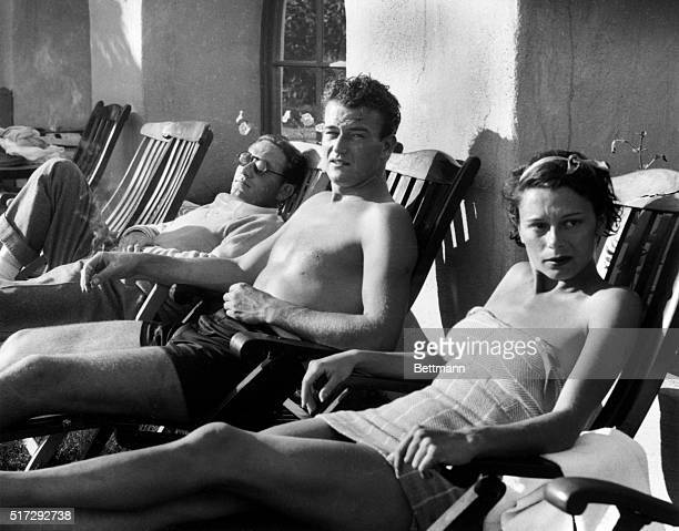 Spencer Tracy reclines in a deck chair next to John Wayne and is wife Josephine Wayne The three relax at El Mirador in Palm Springs California on...