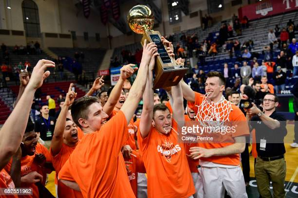 Spencer Weisz of the Princeton Tigers is the first to hoist the trophy for the crowd after the win against the Yale Bulldogs in the Ivy League...