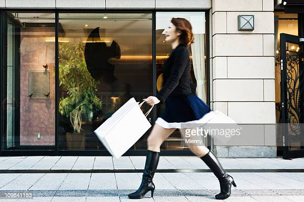 spending spree happy woman shopping with paper bags - high heels short skirts stock pictures, royalty-free photos & images