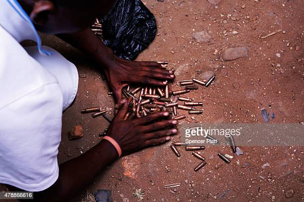 Spent bullet casings are gathered in a street where a man who was killed by police the previous evening on June 28, 2015 in Bujumbura, Burundi....