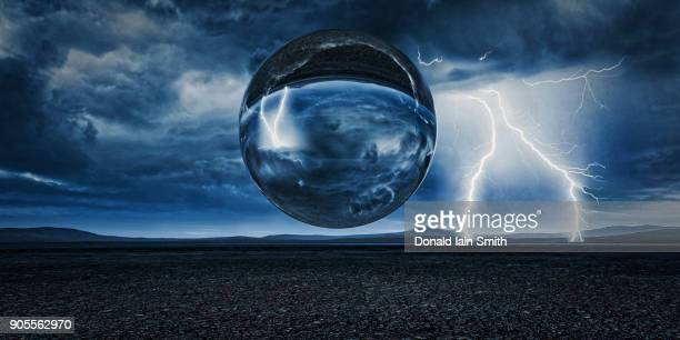 sphere floating in remote landscape - crystal smith stock pictures, royalty-free photos & images