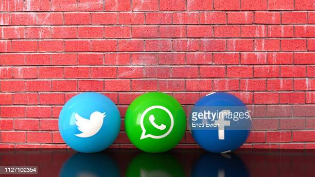 Sphere shape of marble Social media services icons including Twitter, Whatsapp and Facebook with red brick wall