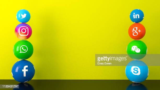 sphere shape of marble social media services icons on yellow desk - community logo stock pictures, royalty-free photos & images