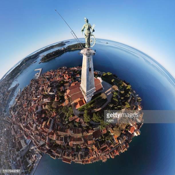 朝、クロアチアのイストリア、聖ユーフェミア教会の鐘楼の上に旧市街ロヴィニと聖エウフェミア像(15世紀)の球面の空中パノラマ。 - 石造りの家 ストックフォトと画像