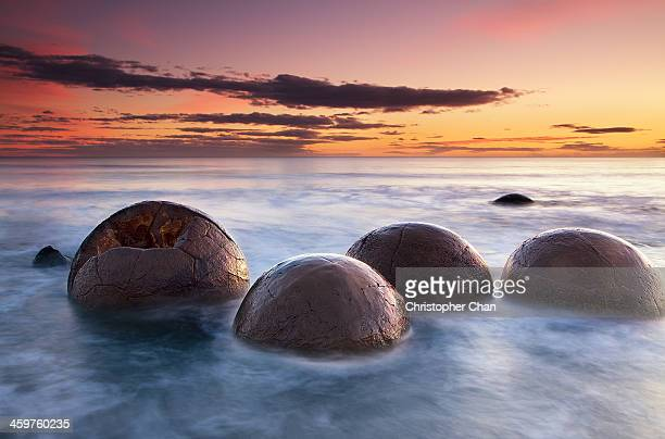 Spherical boulders in the sea at sunrise
