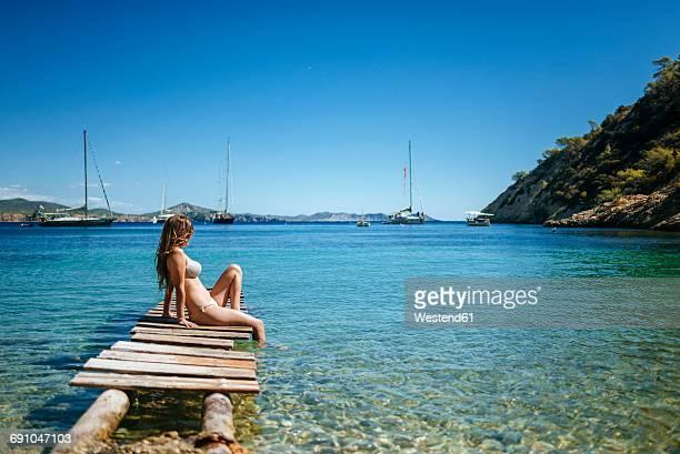 Spian, Ibiza, Woman in bikini sitting on jetty