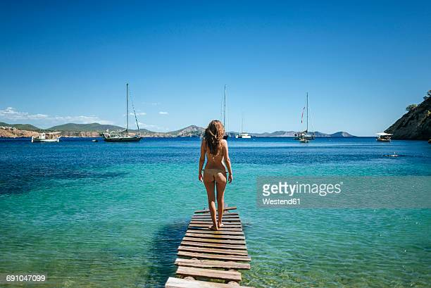 Spian, Ibiza, Woman in bikini standing on jetty, rear view